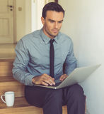 Handsome businessman at home. Handsome businessman in classic suit is using a laptop while sitting on the stairs at home Royalty Free Stock Photo