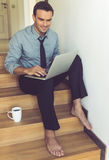 Handsome businessman at home. Handsome businessman in classic suit is using a laptop and smiling while sitting barefoot on the stairs at home Stock Images