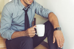 Handsome businessman at home. Cropped image of handsome businessman in classic suit holding a cup of coffee while sitting on the stairs at home Royalty Free Stock Images