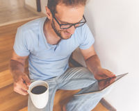 Handsome businessman at home. Handsome young businessman in casual clothes and eyeglasses is using a digital tablet, holding a cup of coffee and smiling while Stock Photo