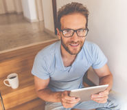 Handsome businessman at home. Handsome young businessman in casual clothes and eyeglasses is using a digital tablet, looking at camera and smiling while sitting Stock Image