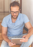 Handsome businessman at home. Handsome young businessman in casual clothes and eyeglasses is using a digital tablet and smiling while sitting on stairs at home Royalty Free Stock Images