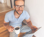 Handsome businessman at home. Handsome young man in eyeglasses is using a digital tablet, holding a cup of coffee, looking at camera and smiling while sitting on Stock Images