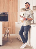 Handsome businessman in kitchen. Full length portrait of handsome businessman using a smart phone, holding a cup, looking at camera and smiling while standing in stock image