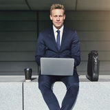 Handsome businessman with laptop looking at camera Stock Photos