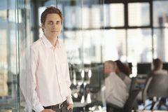 Handsome Businessman Leaning On Office Glass Door Stock Photography