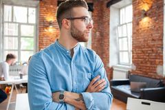 Handsome businessman is looking out the window and smiling while standing in office. royalty free stock photo