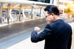 A handsome businessman is looking wristwatch for checking time. royalty free stock photos