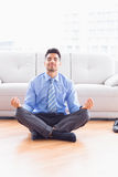 Handsome businessman meditating in lotus pose on the floor Stock Images
