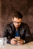 Handsome businessman with modern haircut looking at smartphone Royalty Free Stock Photo