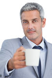 Handsome businessman offering cup of coffee Royalty Free Stock Images