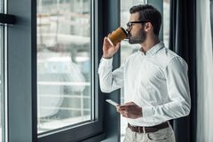 Handsome businessman in office. Handsome businessman in eyeglasses is holding a smart phone and drinking coffee while looking out the window in office Royalty Free Stock Image
