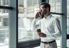 Handsome businessman in office. Handsome businessman in eyeglasses is talking on the mobile phone and drinking coffee while looking out the window in office Royalty Free Stock Images