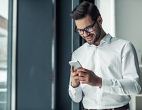 Handsome businessman in office. Handsome businessman in eyeglasses is using a smart phone and smiling while standing near the window in office Royalty Free Stock Photo
