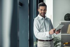 Handsome businessman in office. Handsome businessman is holding a digital tablet, looking at camera and smiling while standing in office Stock Photos