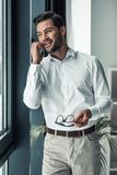 Handsome businessman in office. Handsome businessman is talking on the mobile phone, looking out the window and smiling while standing in office Royalty Free Stock Images