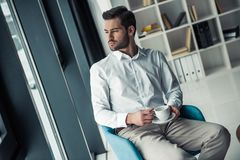 Handsome businessman in office. Handsome pensive businessman is holding a cup and looking out the window while sitting in the chair in office Royalty Free Stock Image