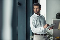 Handsome businessman in office. Handsome pensive businessman is holding a digital tablet, looking out the window and thinking while standing in office Stock Image
