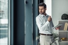 Handsome businessman in office. Handsome pensive businessman is holding a digital tablet, looking out the window and thinking while standing in office Royalty Free Stock Photography