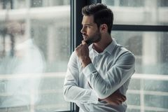 Handsome businessman in office. Handsome pensive businessman is looking out the window, rubbing his chin and thinking while standing in office Stock Photography