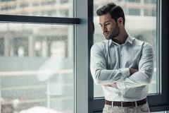 Handsome businessman in office. Handsome pensive businessman is looking out the window, rubbing his chin and thinking while standing in office Royalty Free Stock Image