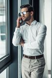 Handsome businessman in office. Handsome serious businessman in eyeglasses is talking on the mobile phone while looking out the window in office Royalty Free Stock Images