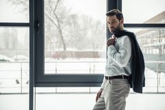 Handsome businessman in office. Handsome businessman is holding his jacket and looking at camera while standing near the window in office Royalty Free Stock Photos