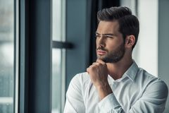 Handsome businessman in office. Portrait of handsome businessman looking out the window, rubbing his chin and thinking while standing in office Royalty Free Stock Images