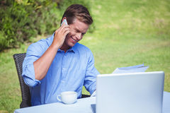 Handsome businessman on the phone reading a document Royalty Free Stock Photography