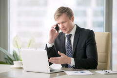 Handsome businessman with phone. Young handsome businessman working with laptop at desk in the modern office, talking on phone, unexpected obstacles, risky stock images