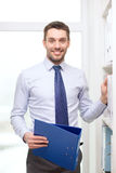 Handsome businessman picking folder at office Stock Photo