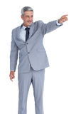 Handsome businessman pointing away Royalty Free Stock Photos