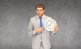 Handsome businessman pointing finger to wall clock. Business, time magement and office concept - handsome businessman pointing finger to wall clock Stock Images