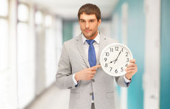 Handsome businessman pointing finger to wall clock. Business, time management and office concept - handsome businessman pointing finger to wall clock Royalty Free Stock Images