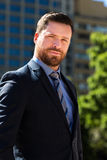 Handsome businessman portrait. Handsome young  businessman with beard posing for the camera.  He has blue eyes and a dark blue outfit.  He is outdoor in front of Stock Images