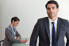 Handsome businessman posing while his colleague is working Royalty Free Stock Photography