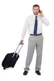 Handsome businessman posing with suitcase and phone Royalty Free Stock Images