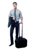 Handsome businessman posing with trolley bag. Happy young man holding his luggage in full length pose Royalty Free Stock Photos