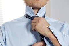 Handsome businessman preparing to official event, straighten tie Stock Image