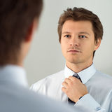 Handsome businessman preparing to official event, straighten tie Royalty Free Stock Image
