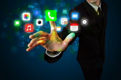 Handsome businessman pressing colorful mobile app icons with bok Stock Image