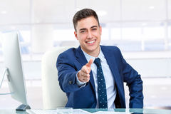 Handsome businessman reaching out hand at desk. Close up portrait of Handsome businessman reaching out hand at desk. Young man in office in front of computer royalty free stock images
