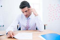 Handsome businessman reading document Royalty Free Stock Photography