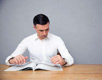 Handsome businessman reading magazine Stock Photography