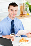 Handsome businessman reading news holding coffee Royalty Free Stock Photography
