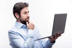 Handsome businessman reading report on laptop