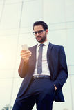 Handsome businessman reading text message on his smartphone Royalty Free Stock Images