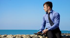 Handsome businessman relaxing with tablet in front of the ocean Stock Photography