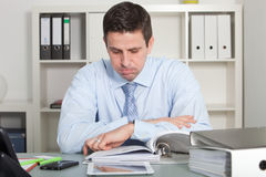 Handsome businessman reviewing report papers Royalty Free Stock Photos