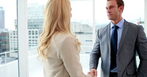 Handsome businessman shaking hands with blonde colleague. In the office stock video